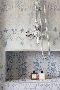 Blue mosaic shower tiles are fitted with a polished nickel shower kit mounted above a tiled shower niche.