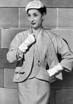 Renée Breton in rose wool-acrilan blend suit, buttonless jacket worn over vest fastened by gold safety pin, by Pierre Balmain, photo by Georges Saad, 1955