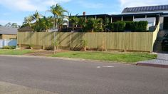 Timber fence with sleeper retaining wall Retaining Wall Fence, Sleeper Retaining Wall, Timber Fencing, Sidewalk, Plants, Ideas, Wood Fences, Wooden Fences, Wooden Fence