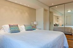 Idéia de cabeceira. Sem cabeceira, mas com luz aconchegante por conta de pontos de luz instalados no teto logo acima da cama.