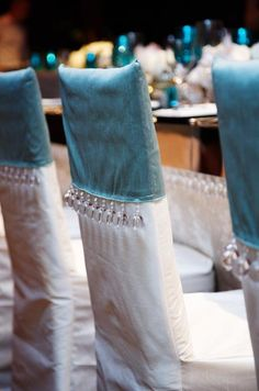 Chairs are covered with white and blue slipcovers trimmed with glass beads.