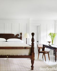 Master Bedroom  Strong-lined furnishings in rich browns lend drama to a white master bedroom. A midcentury woven-leather chair adds a modern touch beside an antique writing table and a 19th-century American cannonball bed from Leonards New England.