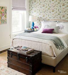 O baú antigo reflete o tom histórico da casa. Travesseiros com monogramas, livros e discos dão personalidade ao ambiente. O papel de parede de folhagens e beija-flores faz da parede o ponto focal.