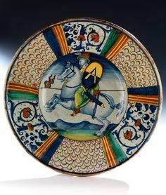 Die große Platte auf kleinem Fußring gemuldet und mit breiter Fahne. Die Fahne ziert ein Schuppendekor sowie alla porcellana -Rankendekor. Im Spiegel ist ein ...