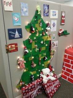 Cubicle Christmas tree created from a large piece of cardboard covered with squares of tissue paper.  The lights and ornaments add a little life.  Finished off with Christmas cards and empty boxes wrapped as gifts.