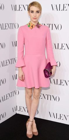 Emma Roberts wearing a pink Valentino frock featuring a playful floral collar, with a studded plum clutch and tan ankle-strap pumps.