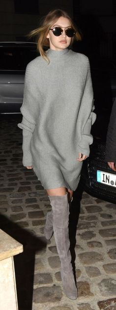 Gigi Hadid wears a ribbed tunic-style Designers Remix sweater dress, grey Stuart Weitzman over-the-knee boots, and sunglasses: