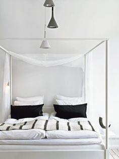 A thin piece of white silk fabric draped over the bed creates a semi-canopy. Photo by Marcus Lawett via Residence.
