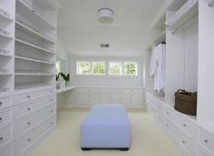 Lynn Morgan Design: Huge walk-in closet with white built-in shelves & cabinets, built-in vanity and blue ...