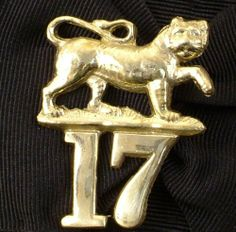 British 17th Regiment Cap Badge by International Military Antiques, Inc.. Raised in two Battalions in 1688 which became the LEICESTER Regiment after 1881. Prowling Tiger over numbered 17 cap badge with all black glengarry.
