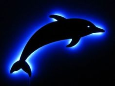 """Dolphin Silhouette Glow Art by HL Carvings. $42.00. www.HLCarvings.com. 12"""" High x 26"""" Wide. Uniquely designed and crafted in the USA by HL Carvings. Turn any room or office into a serene tropical getaway with this handcrafted dolphin silhouette. The beautiful ocean blue glow that surrounds this piece is not only stunning but energy efficient LED lighting which uses extremely low energy so you can enjoy the effect all day and night. Perfect for using as a night lig..."""