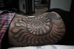 A Thomas Hooper tattoo of a nautilus shell. Even in black ink, the trippy nature of the nautilus is apparent
