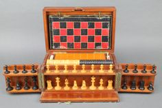A 19th Century mahogany games compendium comprising a Staunton chess set, set of draughts, set of bone dominoes, 6 bone die, 4 crib markers, crib board, 7 bone cubes marked 1-6 and 1 decorated a cotton reel and 62 cards comprising 2 part sets of un numbered spade cards comprising 2 Kings, 2 Queens, 2 Jacks, 2 tens, 2 nines, 2 eights and 2 sevens, 2 parts sets of hearts - 2 Kings, 2 Queens, 2 Jacks, 2 tens, 2 nines, 2 eights, 2 sevens and 2 aces, 2 part sets of clubs - 2 Kings, 2 Queens, 2…