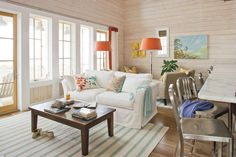 Crisp whites combined with punches of bright colors immediately transport you to the coast. In this living room, aqua accents in the pillows, throw, and rug mimic the ocean's dazzling blues, and the pops of bright orange are inspired by the magnificent hues of the setting sun. Whitewashed horizontal shiplap planking evokes the feel of old Gulf-front beach houses.  See this Coastal Home