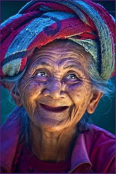 A colorful lady from India whose smile is brighter than anything she is wearing.