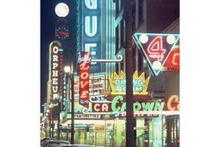 1960 at night of the entertainment strip on Granville Street downtown. Photo includes neon signs for the Vogue Theatre, Herbert Love, the Orpheum Theatre, the Crown Dining Room, as well as stores and parked cars. Photograph by: Ken Oakes , Vancouver Sun