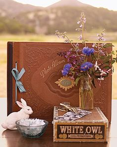 Flea market finds like the cigar box, ceramic rabbit, and vintage photo album lend the guest-book table rustic charm.