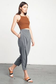 Grey Pleated Cropped Trousers - A gorgeous pair of trousers done in a versatile shade of medium grey and a cool, slouchy fit. Modern take on the trouser - these pants fit baggier and looser on top and tapers down at the ankles. The pleated front adds a sleek detail and the shape of the pants are super flattering. Fabric is done in a woven fabric, and is soft to the touch.