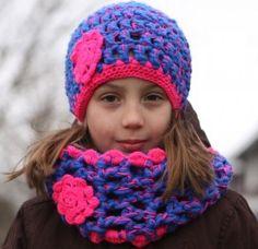 Lekker warme muts met bijpassende sjaal. Versierd met knal roze.De sjaal kan je lekker twee keer om je nek wikkelen.