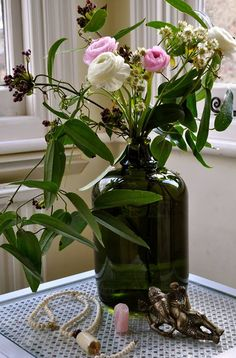 Ranunculus, astrantia & clematis in recycled glass vase www.vanessabirleyflorals.com