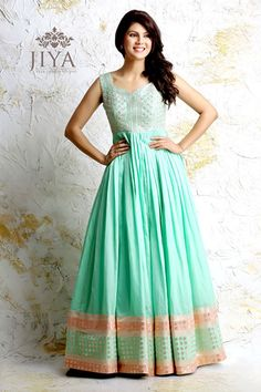 Yards of fresh mint green chanderi pleats flowing down from the empire line, styled with panels of chanderi buttis in self and peach. The torso panel is embroidered in dori in jaal design, gracefully styled with a cutout back. The outfit comes with a matching net dupatta and churidar.