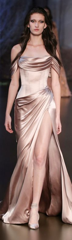 Ralph & Russo Haute Couture Fall Winter 2015-16 collection.There is a lot to love about this dress:A very sensual satin is perfect and this shade compliments women with cool tones.The dropped sleeves,(which rest low on the shoulders) with draping around the low neckline. I love this tight bodice with boning.The rusched skirt is part of what creates the high front slit.The shoes are a nice touch, being left strapless creates a longer and leaner line even if this dress is for curves!