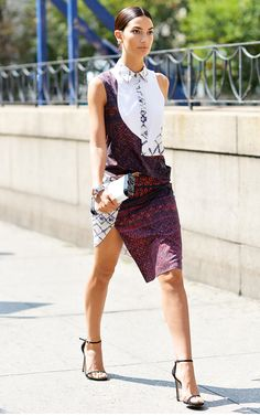 Lily Aldridge wears a mixed print shirtdress with a statement slit, minimal clutch bag, and black heeled sandals