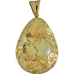 """A fine vintage 14K gold openwork jadeite pendant, c. 1920s. The jade is a pale green color, polished smooth, with ornate gold decoration in the form of phoenix birds with foliage and the moon. It is not marked, but tests 14K. There is a nice sized bale to allow for a thicker gold chain. The pendant measures 2 1/4"""" in height and 1 1/4"""" in width. It weighs 15.8 grams and is in excellent condition."""