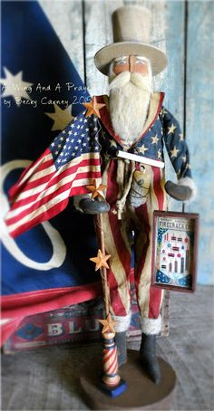"""Olde Firecracker Sam is a OOAK (one of a kind) Uncle Sam with loads of Americana Detail...  He is mounted on a large primitive wood base and stands 19"""" tall to the top of his hat. Made of muslin, he has hand painted blue eyes, a stitched sculpted nose and blushed cheeks. His beard brows and hair are made of a coffee stained felted wool roving. He has wired arms and painted on black gloves and boots. He is dressed in Red and White stripe cotton pants, a Blue print Pledge of Allegiance"""