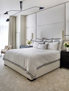 "A floor-to-ceiling upholstered panel adds coziness in the mostly monochromatic master bedroom. ""In a way, this room was a compilation of all the other spaces,"" says the designer. ""We were very literal about the cream, black, and white palette."" The sculptural ceiling lamp by Serge Mouille is from Design Within Reach."
