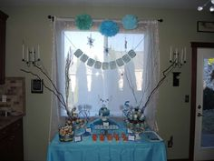 "Frozen Themed Dessert and Snack table. Changed out our normal curtains to sheer white curtains backlit with white Christmas lights. Hung pom-pom's and snowflakes and a ""Let it Go"" banner from the ceiling."