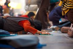 A Tibetan woman in mid-prostration at the Jokhang temple in Lhasa