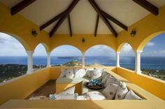 I love the sunny yellow color they chose for this pavilion. With dozens of pillows, this comfy seating area offers a lovely vantage point from which to enjoy this panoramic view. Tropical porch by Dan Forer