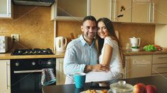 Portrait of happy smiling couple sittting in the kitchen early morning at home. Romantic