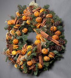 Sweetly scented dried oranges and 'smells like Christmas' cinnamon sticks make the perfect festive statement for the front door.