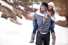 Man and woman Piggy back riding in the snow in colorado