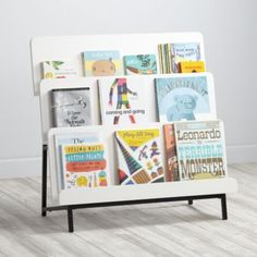 """Our New Issue Bookcase is a new take on your standard bookcase.  Featuring a three-tier design that allows the books to display forward facing, it's a great way to let the little ones see and reach their favorite books. Details, details Nod exclusive A Royce Nelson design Three tier design allows children of all ages to reach their favorite books Top shelf is 10"""" high, middle shelf is 11"""" high and bottom shelf is 13"""" high; all shelves are between 2."""