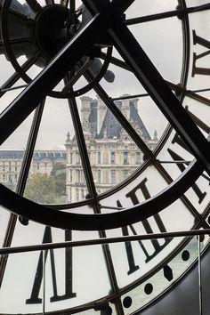View through giant clock in Musée d'Orsay over Musée du Louvre, Paris France by Brian Jannsen