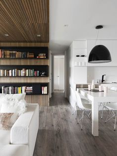 wood wall/ceiling surround + deep sofa + book shelves + white cabinetry + oversized pendant