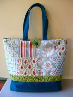 This tote bag is made using a handy charm pack and is embellished with a gathered wrap-around band separating the base of the bag from the patchwork. Very