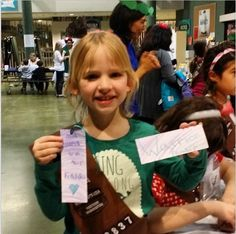 A girl scout shows her bookmarks. Girl Scout Service Unit 422