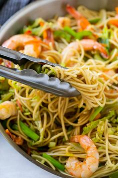 A pile of chow mein noodles with shrimp and veggies.