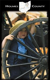 Amish boy looking through a carriage wheel