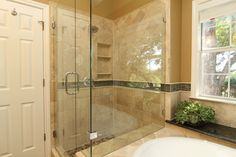 x This beautiful frameless shower is adjacent to the master tub. Lots of natural light comes in through the windows in this bathroom making everything shine.