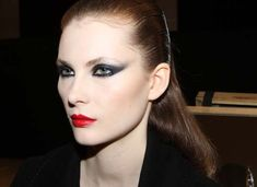"""elongated eyes and a heavily rouged mouth, he created backstage for the show. """"We worked more with powder than foundation, to create the face's matte canvas,"""" said Espinet, who used MAC's Feline Kohl eye pencil to emphasize the eyes, which were layered with gray eye shadow and finished with a midnight blue sparkle. Taupe blush was used to contour cheekbones, and the pout was created by blending orange and red lip shades."""