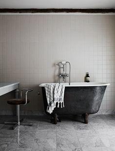 marble floor tiles in the bathroom. Black bath with scandinavian style accessories.