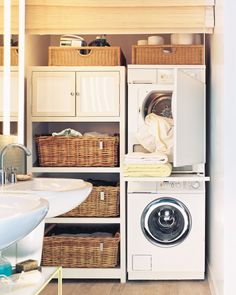 A laundry workstation and storage area fit along the far right wall of the room. The stacked, European-style washer-dryer set is a great space saver; a shelf between the machines pulls out for folding items fresh from the dryer, then slides out of sight. Shelves hold baskets for sorting laundry, and the cabinet makes convenient towel storage. Bathroom and laundry supplies are kept in baskets on top of the units. A matchstick shade lowers all the way to the floor, gracefully hiding the…