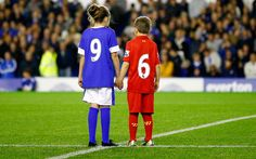 Children wearing Everton and Liverpool jerseys pay their respects to the 96 victims of the Hillsborough disaster before the Premier League match between Everton and Newcastle United at Goodison Park in Liverpool