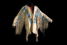 "Blackfoot Beaded Hide War Shirt, thread and sinew-sewn, beaded panels overlaid across shoulders and chest with slit tipi designs executed in colors of rose, greasy yellow, cobalt, and light blue; triangular bib made of navy and red wool; fringe falls along arm; length 28"" x chest 50"". Included is a copy of a photograph showing a Blackfoot man wearing the shirt."