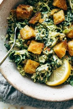 Brussels & Kale Caesar! Papery-thin shreds of brussels sprouts and chopped lacinato kale, tossed with a creamy, garlicky, avocado-based vegan caesar dressing, topped off with the most addicting cheezy garlic croutons. YUM. #salad #vegan #caesar | pinchofyum.com